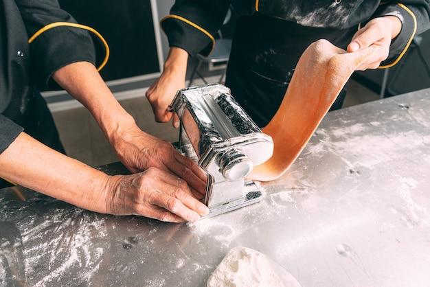 Due abili cuochi stanno facendo la pasta utilizzando una macchina speciale.