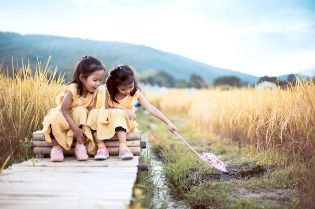 Due ragazze asiatiche felici del piccolo bambino divertendosi da giocare insieme e sedendosi sul passaggio pedonale di bambù nella risaia nel tono d'annata di colore