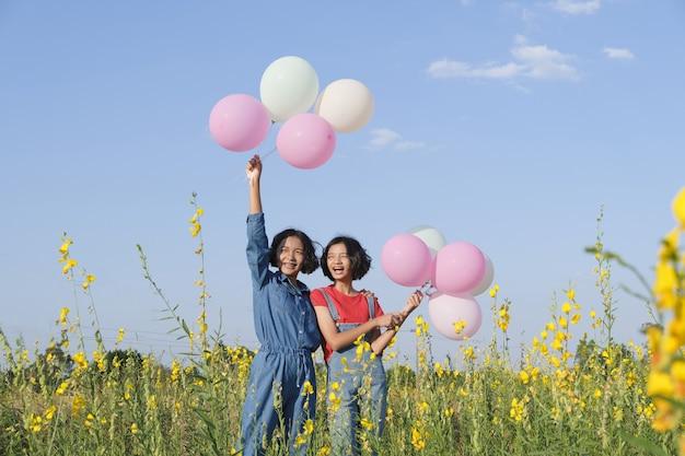 Due ragazze asiatiche felici al giardino fiorito in estate con un bel cielo