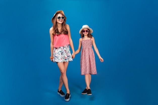 Due belle sorelle felici che sorridono e camminano insieme su sfondo blu