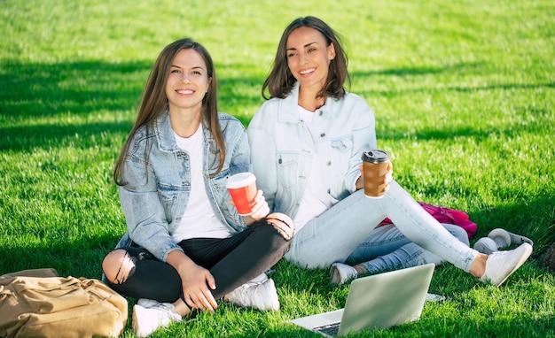 Due amici di ragazza felice bella giovane studentessa in abiti casual in denim sono rilassanti nel parco del college con laptop e smartphone dall'università e bere caffè