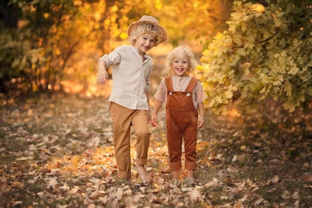 Due ragazzi felici stanno giocando nel parco all'inizio dell'autunno
