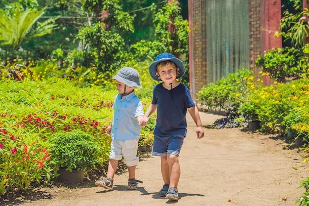 Due fratelli felici che corrono insieme su un percorso del parco in un parco tropicale