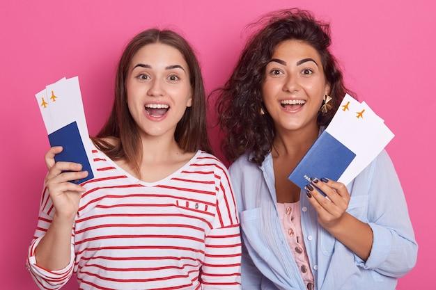 Due ragazze felici del brunette in vestiti variopinti che tengono passaporto Foto Premium