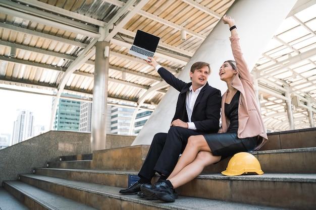 Due genti di affari felici che celebrano il successo con le braccia in su