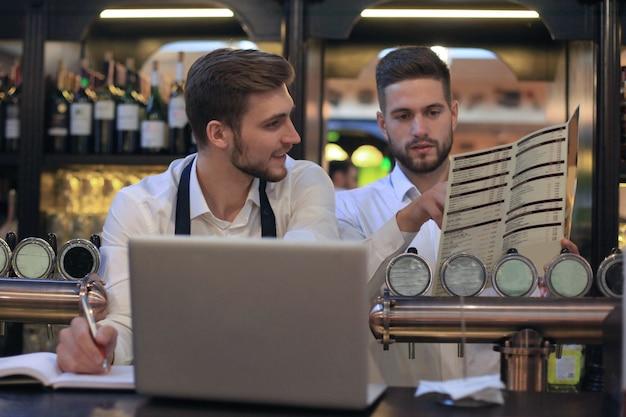 Due gestori felici del caffè che lavorano al computer portatile.