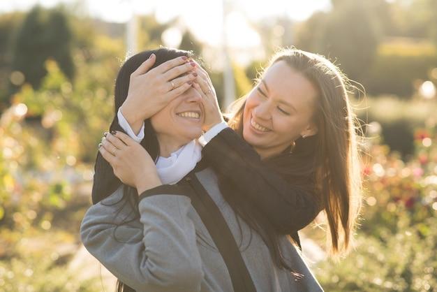 Due ragazze castane caucasiche felici nella sosta soleggiata di autunno. amici giocosi.