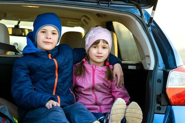 Due bambini felici ragazzo e ragazza seduti insieme nel bagagliaio di un'auto.