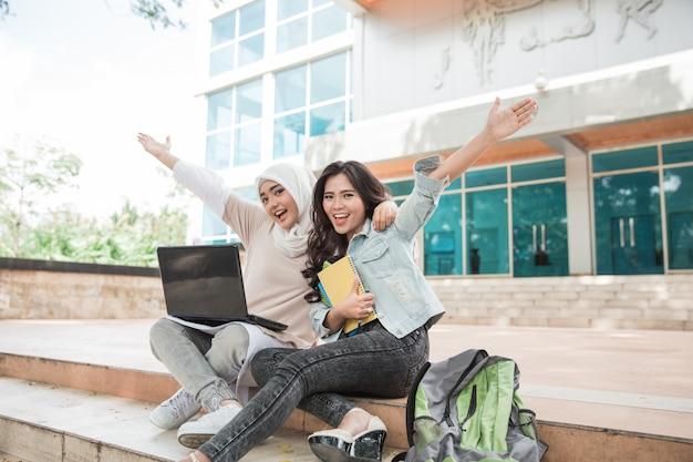 Studente di college felice due che per mezzo del computer portatile