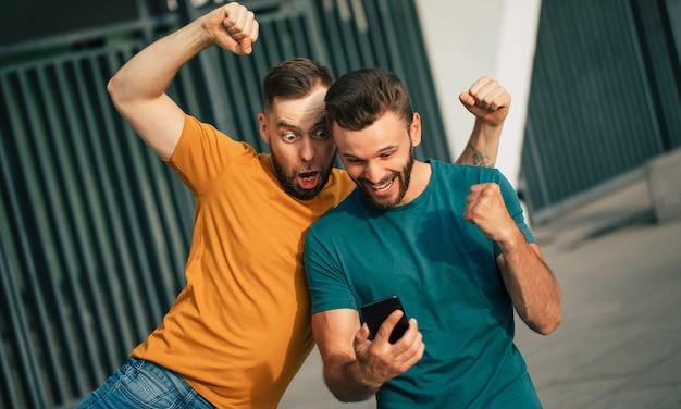 Due amici fan eccitati felici in euforia dopo aver vinto una scommessa con uno smartphone in mano