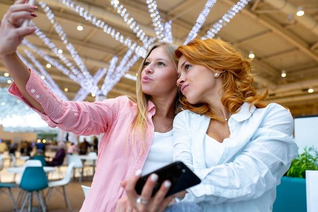 Due amici felici sta prendendo selfie durante lo shopping nel centro commerciale