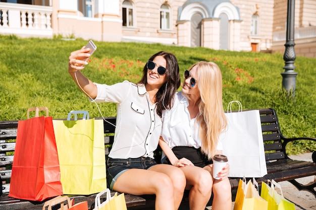 Due amici felici che prendono selfie mentre riposa sulla panchina dopo lo shopping