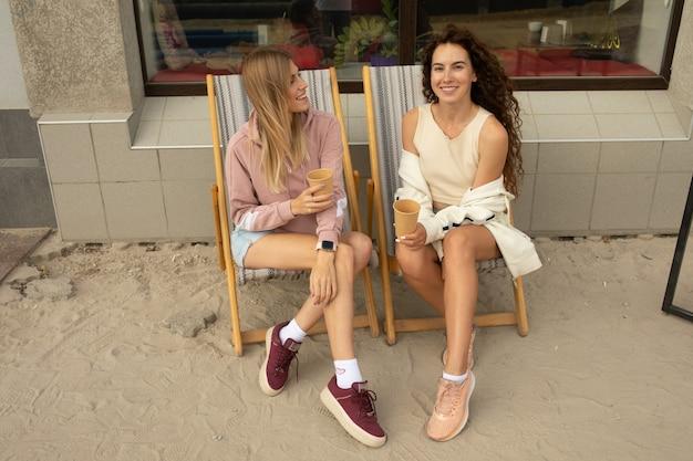 Due amici felici che parlano tenendo una conversazione in una caffetteria