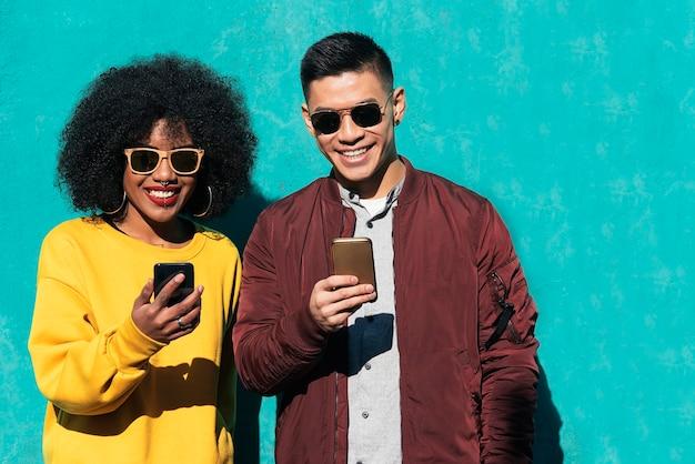 Due amici felici che usano il cellulare per strada. concetto di amicizia.