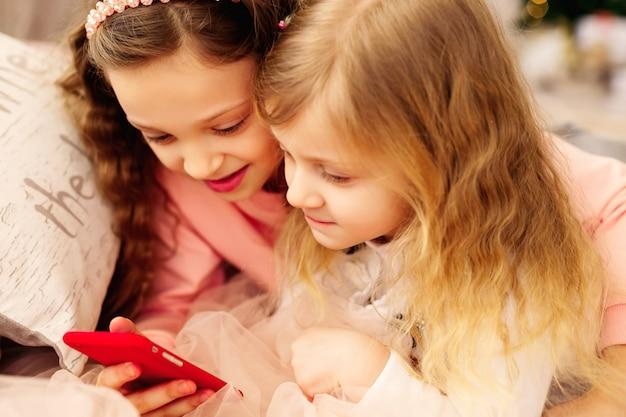 Due ragazze felici sono felici di vedere le foto sul loro cellulare