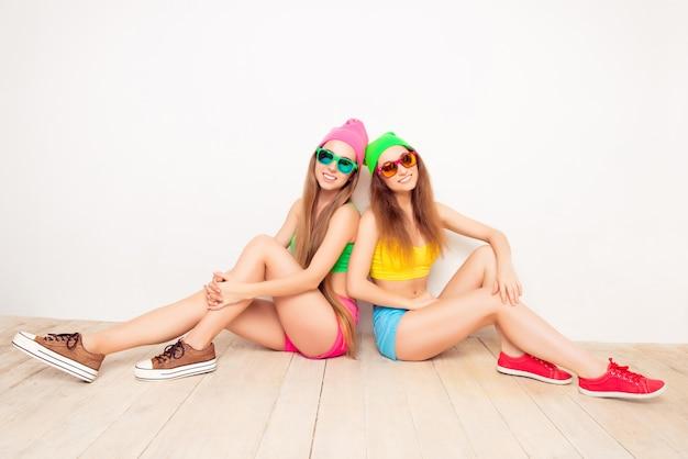 Due ragazze felici in berretti e bicchieri ubicazione sul pavimento