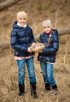 Due ragazze felici a caccia di uova di pasqua nella foresta