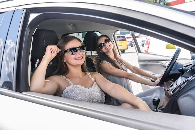 Due ragazze felici che sorridono e che viaggiano in macchina