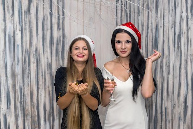 Due ragazze felici con champagne e coriandoli in posa in studio