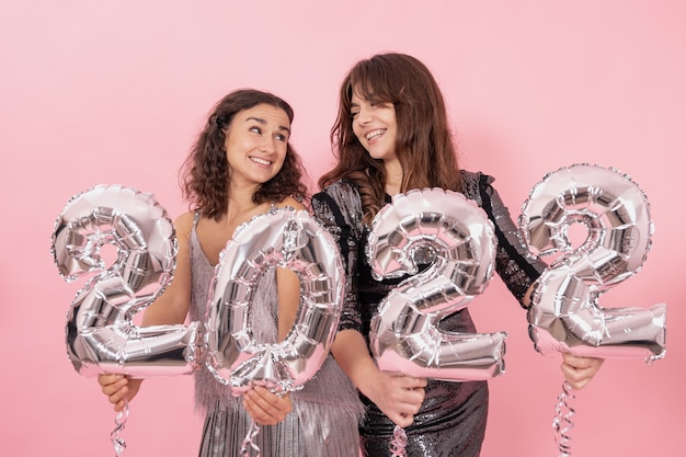 Due ragazze felici con palloncini in lamina d'argento a forma di numeri