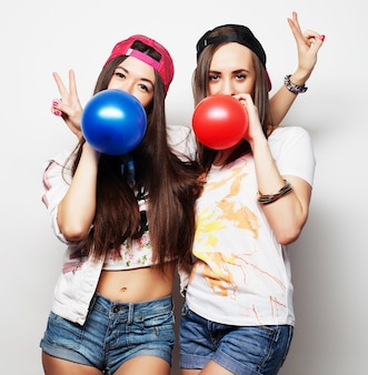 Due ragazze felici hipster sorridendo e tenendo palloncini colorati su sfondo bianco