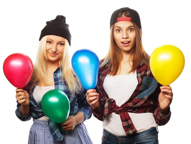 Due ragazze hipster felici che sorridono e tengono in mano palloncini colorati su sfondo bianco