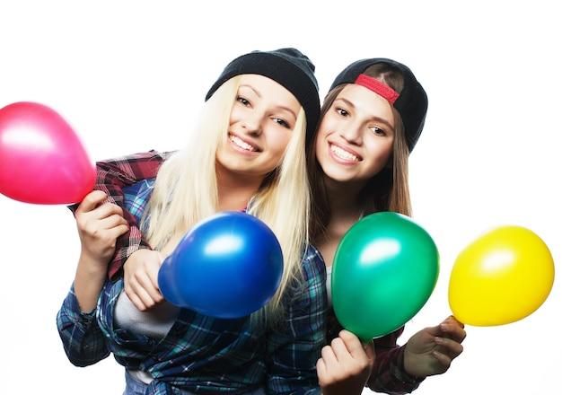 Due ragazze felici dei pantaloni a vita bassa che sorridono e che tengono i palloni colorati sopra bianco