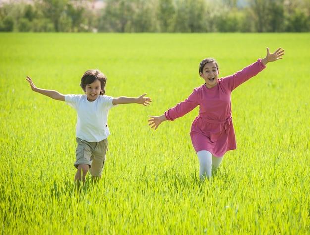 Due bambini felici nel grano verde