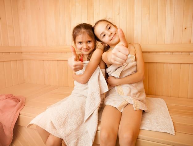 Due bambine felici nella sauna che mostrano i pollici in su