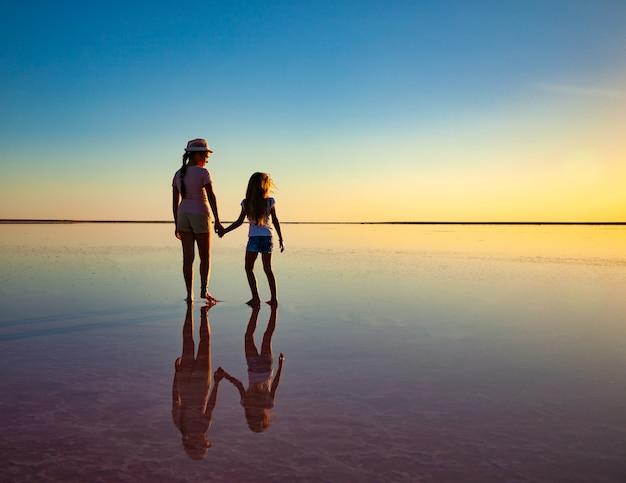 Due sorelle adorabili felici stanno camminando lungo il lago salato dello specchio godendosi il tramonto infuocato di sera