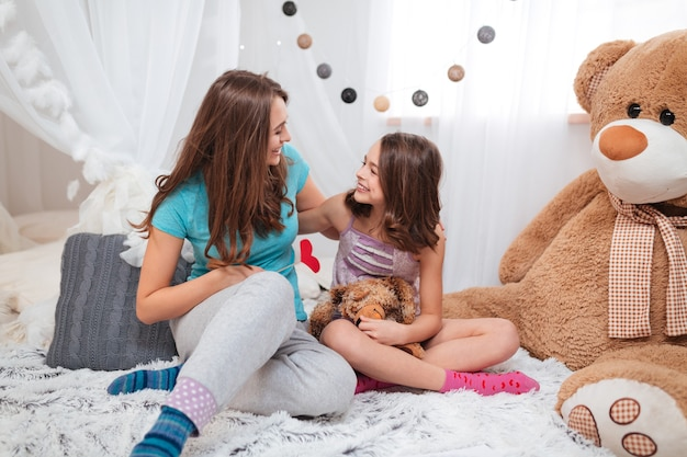 Due sorelle adorabili felici sedute e abbracciate nella stanza dei bambini a casa