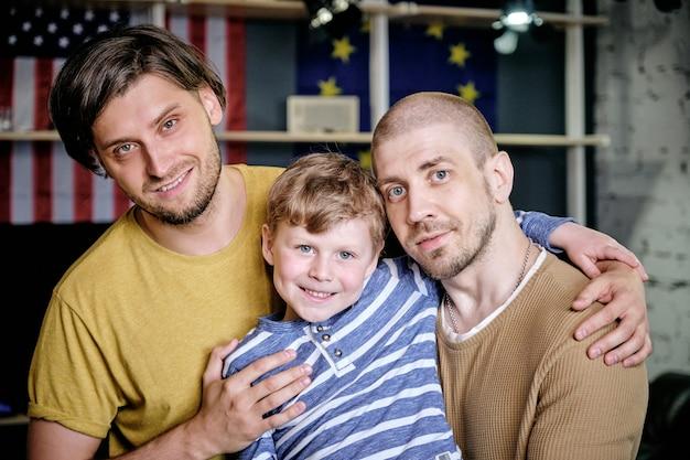 Due uomini felici e un ragazzino in piedi davanti alla telecamera
