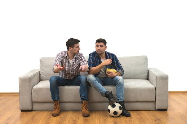 I due uomini felici guardano una partita di calcio sul divano sullo sfondo del muro bianco