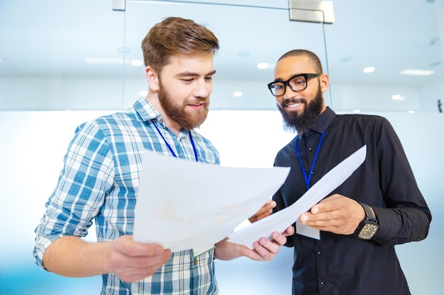 Due uomini d'affari moderni felici che parlano e guardano i documenti in ufficio