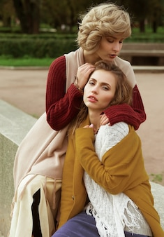 Due donne abbastanza giovani felici, riprese di moda. all'aperto.