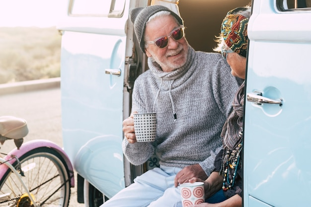 Due anziani felici e una coppia sposata matura che viaggiano insieme per il mondo con un furgone blu e bianco - seduti sul furgone con una tazza di caffè o tè - stile di vita di viaggio anziano e pensionato