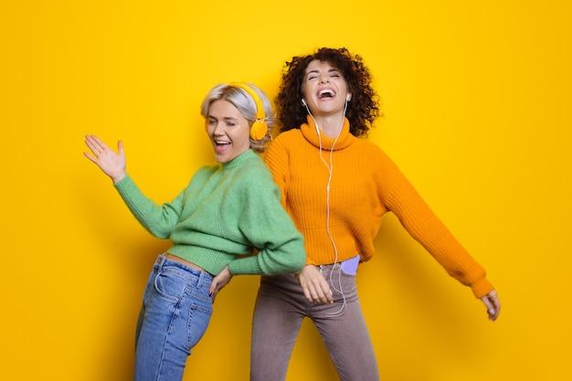 Due sorelle felici con i capelli ricci che ridono mentre indossano le cuffie su una parete gialla