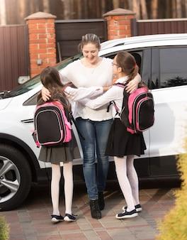 Due ragazze sorridenti che corrono dalla madre incontrandole dopo la scuola