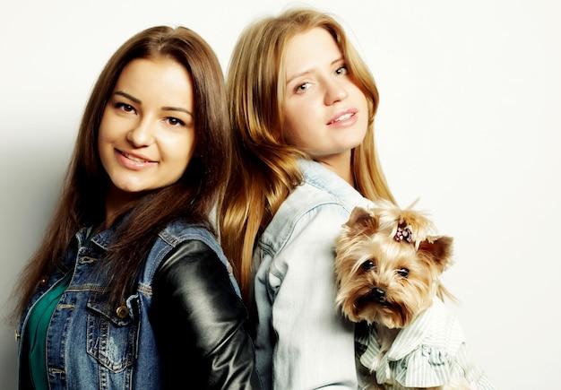 Due sorelle adolescenti felici con lo yorkshire terrier