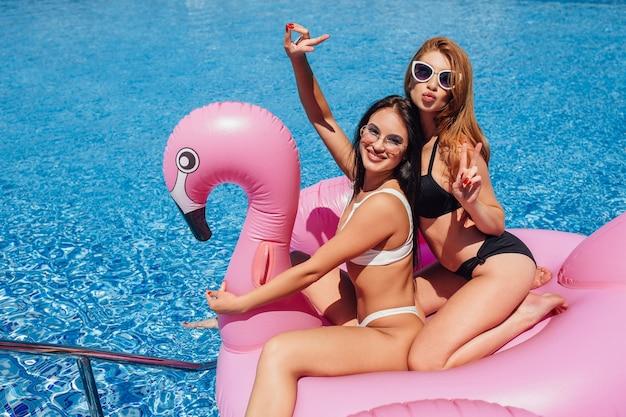 Due donne felici che si divertono su fenicotteri gonfiabili in piscina e tempo soleggiato