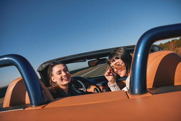 Due donne felici nella cabriolet che guidano e si divertono vista posteriore