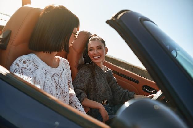 Due donne felici in cabriolet che guidano e si divertono
