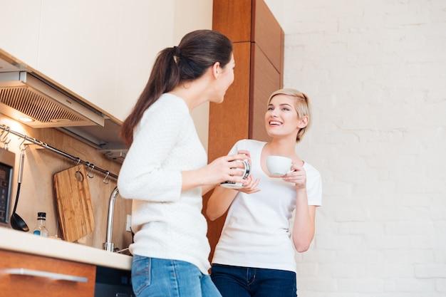 Due donne felici che bevono caffè e spettegolano in cucina