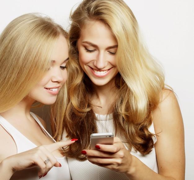 Due amiche felici che condividono i social media in uno smartphone, su sfondo grigio
