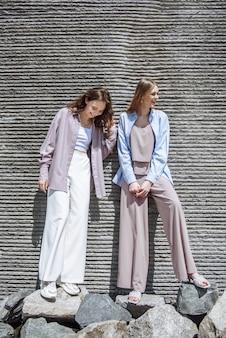 Due modelli di donne felici in posa in abiti alla moda sullo sfondo di un muro in una strada cittadina. concetto di stile di vita
