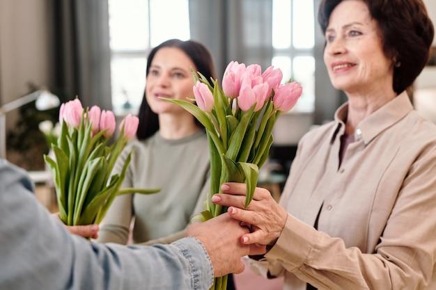 Due donne felici che prendono i tulipani rosa dalle mani dell'uomo
