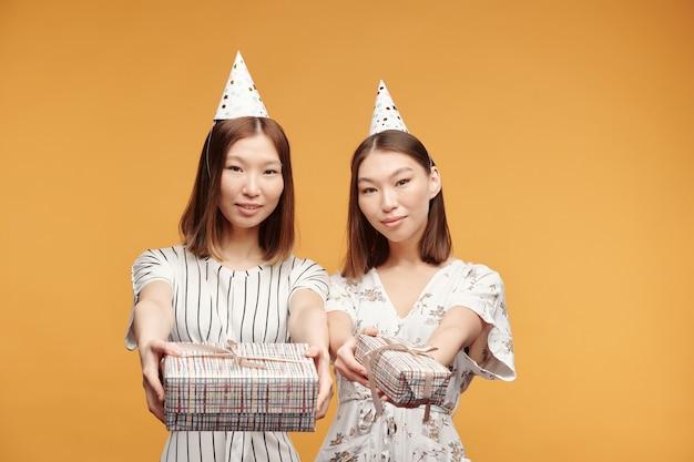 Due giovani e belle gemelle felici in abiti eleganti e cappellini di compleanno che ti guardano mentre passano scatole regalo confezionate con regali