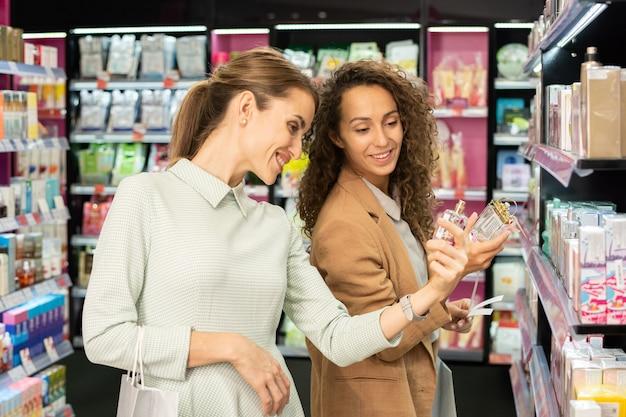 Due giovani acquirenti femminili felici con bottiglie di profumi che scelgono una nuova fragranza nel reparto di bellezza mentre vanno a testare due profumi