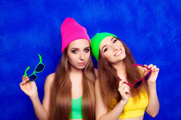 Due giovani amiche felici in cappelli di colore che tengono i vetri