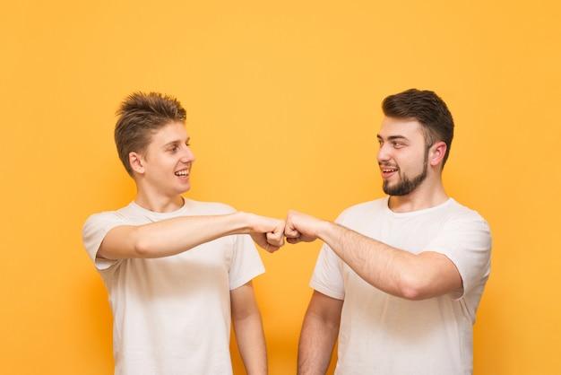 Due giovani felici che danno l'urto del pugno isolato sopra giallo. due uomini felici in magliette bianche danno un pugno e sorridono.